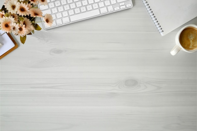Weißer hölzerner schreibtischcomputer, blume und zubehör des büros.