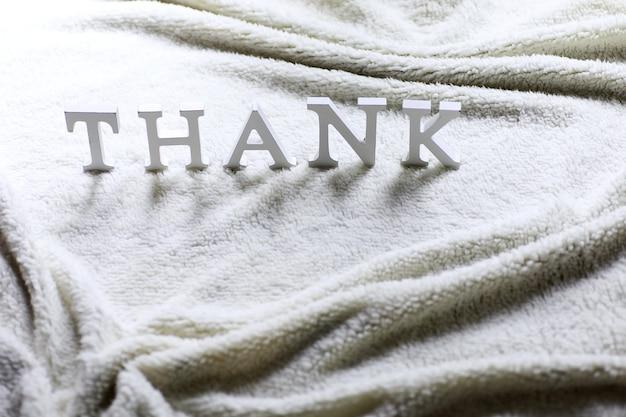 Weißer holzbuchstabe danke auf dem zerknitterten teppich auf dem boden