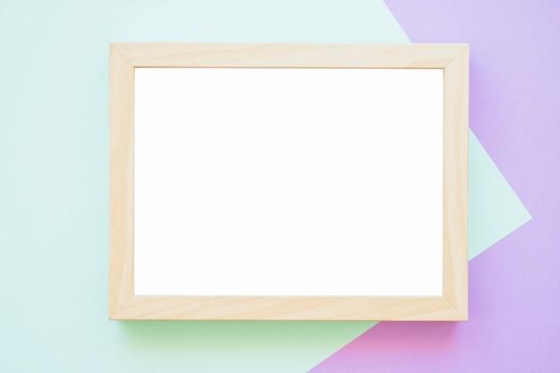 Weißer holzrahmen auf grünem und purpurrotem hintergrund