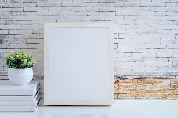 Weißer holzrahmen, bücher und houseplant auf weißer tabelle mit alter backsteinmauer und kopienraum.