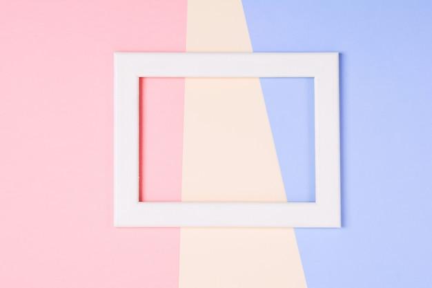 Weißer holzrahmen über buntem papierhintergrund des pastells