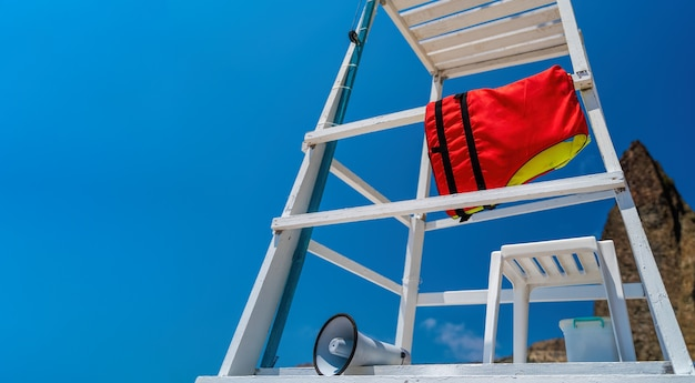 Weißer holzrettungsbeobachtungsposten am strand mit roter schwimmweste und weißem lautsprecher oder hornmegaphon für wichtige öffentliche informationen gegen blauen himmel. speicherplatz kopieren. konzept der sicherheit am strand