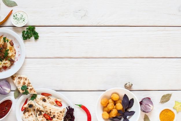 Weißer holztisch mit frühstücksrand flach lag. draufsicht auf rahmen der köstlichen snacks auf weiß