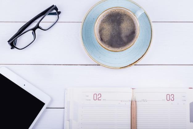 Weißer holztisch mit tablette, schwarzem kaffee, stift, tagebuch und gläsern. draufsicht mit kopierraum