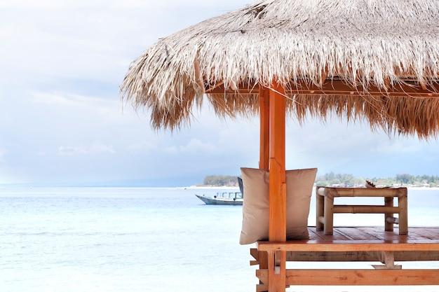 Weißer holzunterstand mit strohdach von der sonne am strand in bali oder thailand. insel gili