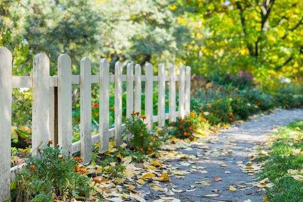 Weißer holzzaun in einem park unter den bäumen, blumen und büschen an einem sonnigen herbsttag