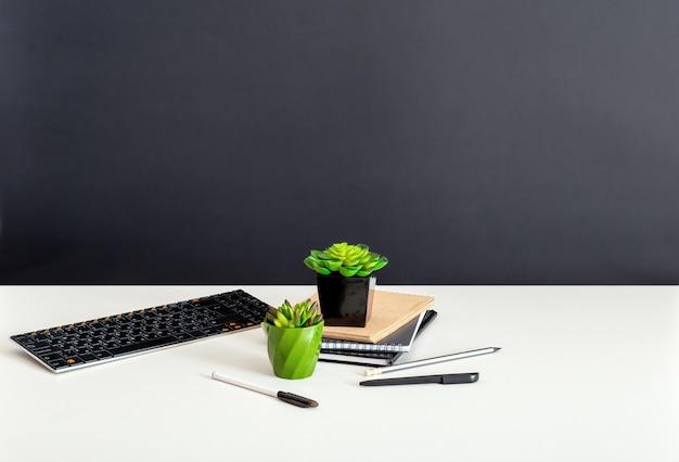 Weißer home-office-tisch mit kopienraum auf schwarzem hintergrund. computernotizblöcke und saftige blumen. tastaturbriefpapier am home-office-arbeitsplatz für remote-arbeit.