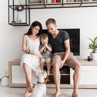Weißer hund, der die lächelnden jungen paare sitzen mit ihrem sohn vor fernsehen betrachtet