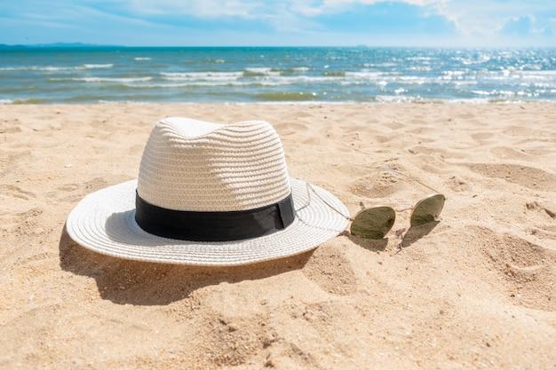 Weißer hut und sonnenbrille auf strand, sommerkonzept
