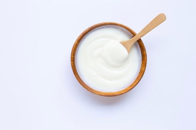 Weißer joghurt in der hölzernen schüssel auf weiß
