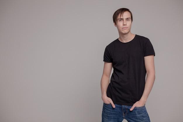 Weißer junger mann in einem schwarzen t-shirt und in den jeans. emotion.