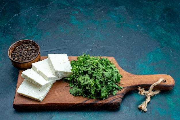 Weißer käse der vorderansicht mit frischem grün auf dem dunkelblauen hintergrund.