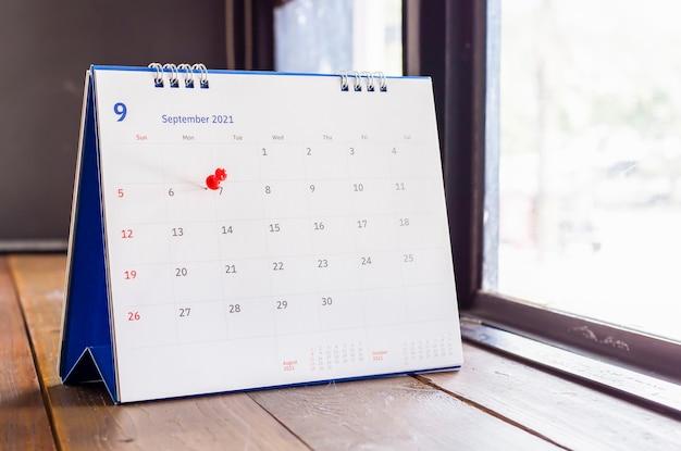 Weißer kalender auf holztischplanungskonzept