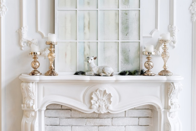 Weißer kaminsims mit kerzen und weihnachtsschmuck. klassisches interieur.