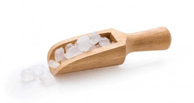 Weißer kandiszucker in der holzschaufel auf weißer wand