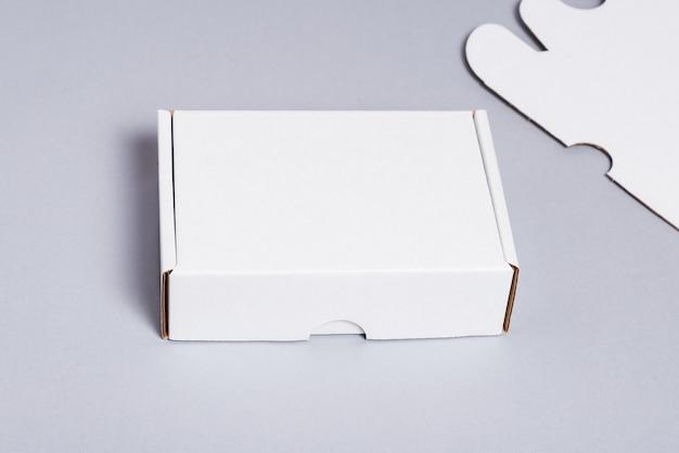 Weißer karton auf grauem hintergrund, draufsicht