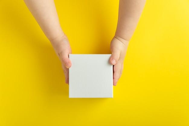 Weißer karton in kinderhänden, gelber hintergrund. draufsicht. speicherplatz kopieren, verspotten.