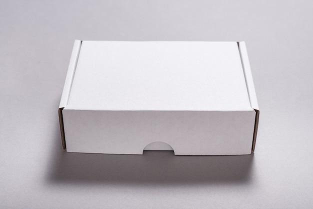 Weißer kartonkarton für den postversand auf grauer oberfläche