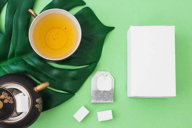 Weißer kasten, kräutertee, zuckerwürfel und teebeutel auf grünbuchhintergrund