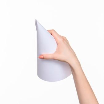 Weißer kegel der requisiten in den weiblichen händen auf weißem hintergrund mit rechtem schatten