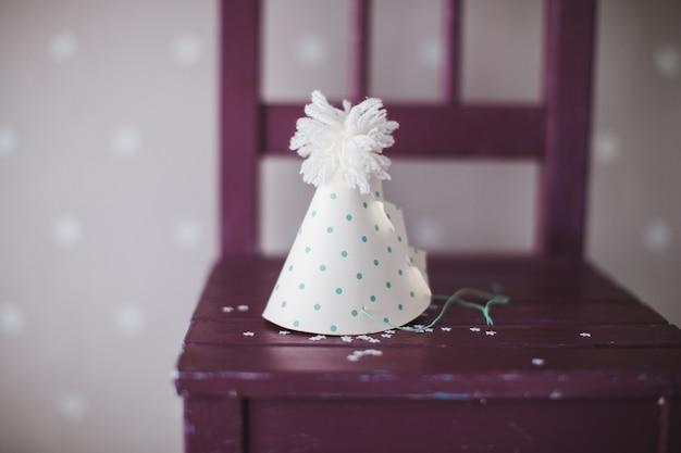 Weißer kegelclownhut mit grünen punkten auf einem stuhl
