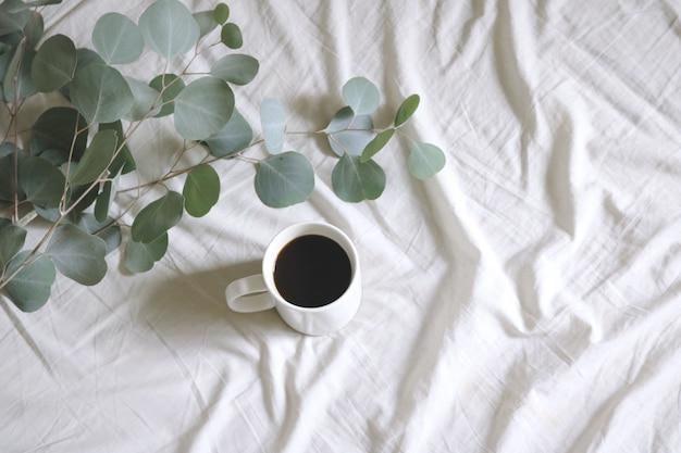 Weißer keramikbecher mit kaffee neben silberdollar-kaugummibaumblättern auf weißem bettlaken