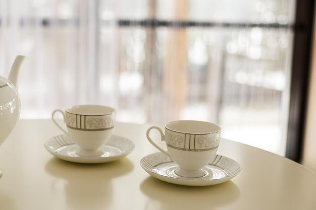 Weißer kessel und zwei tassen tee auf dem tisch.