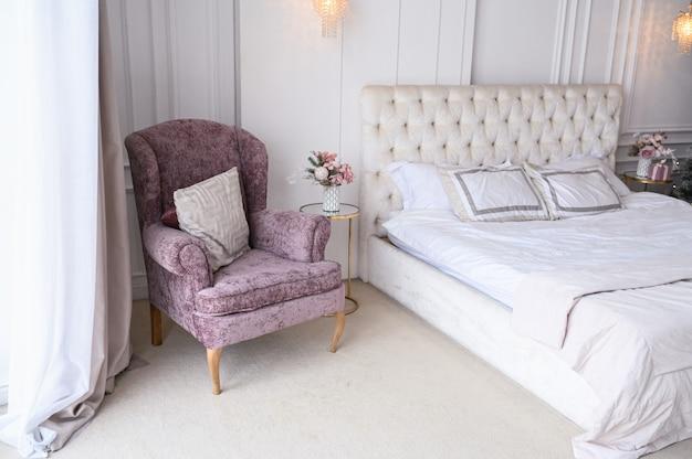Weißer klassischer schlafzimmerinnenraum mit dem feiertagsblumenstrauß des neuen jahres in einem vase