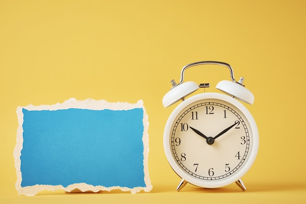Weißer klassischer wecker der weinlese mit glocken und leerem blau zerrissenem papierblatt auf dem gelben. design leer für zeitkonzept