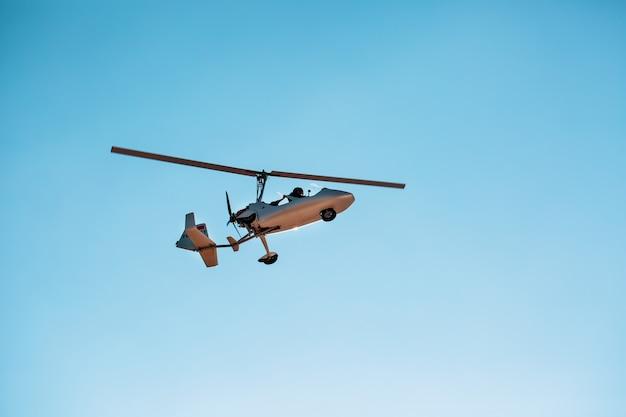 Weißer kleiner autogyro des doppelten gyroplane ohne eine kabine gegen den blauen himmel