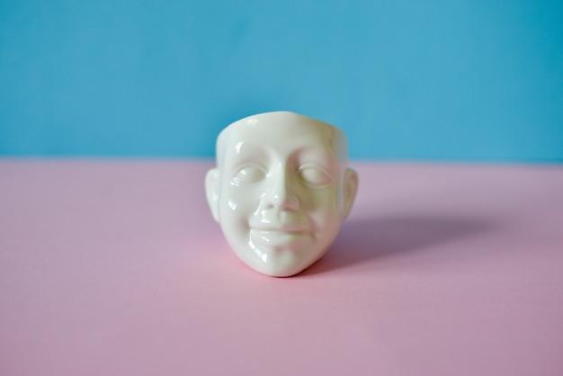 Weißer kopf auf rosa blauem pastellhintergrund