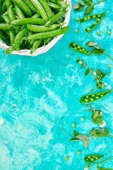 Weißer korb mit frischen grünen erbsen auf blauem hintergrund.