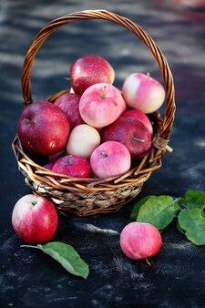 Weißer korb mit rosa reifen äpfeln