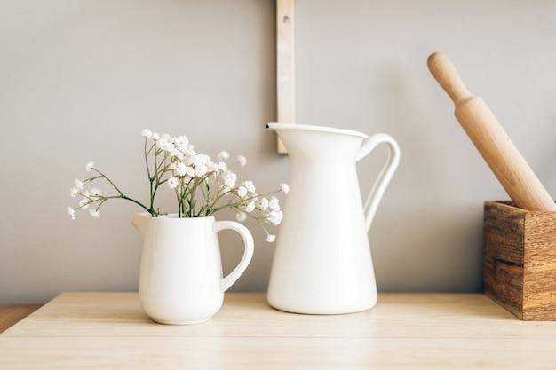 Weißer krug und blumen in einer vase auf einem holztisch in der küche