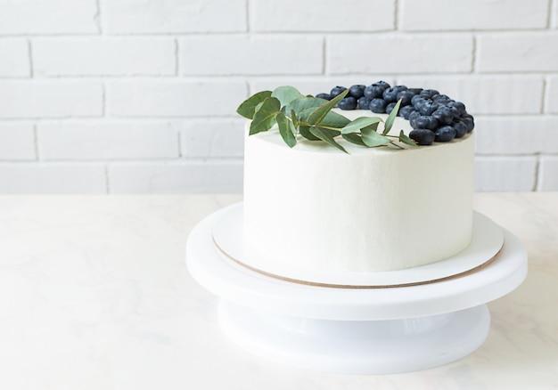 Weißer kuchen auf einem ständer mit blaubeeren und einem zweig eukalyptus in der küche. kuchen mit minimalistischem dekor und kopierraum.
