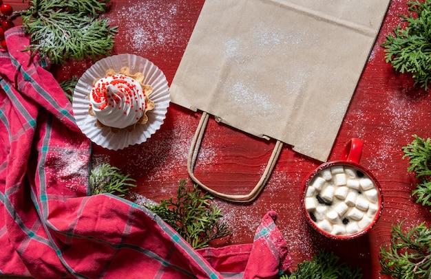 Weißer kuchen auf rotem holztisch mit roter tasse kaffee und einkaufstasche, lieferkonzept.