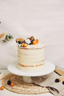 Weißer kuchen mit beeren und passionsfrüchten mit pflanzen dahinter