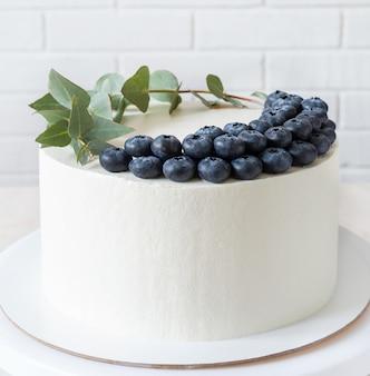Weißer kuchen mit blaubeeren und einem zweig eukalyptus. kuchen mit minimalistischem dekor und kopierraum.