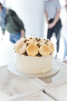 Weißer kuchen mit buttercremeblumen verziert auf stand.