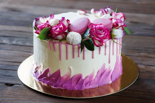 Weißer kuchen mit einer rosendekoration auf einem holztisch