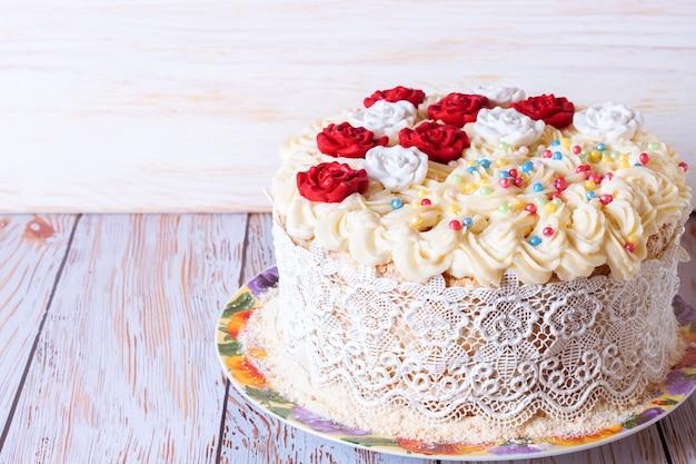 Weißer kuchen mit sahne und roten rosen auf weißem hölzernen backghound.