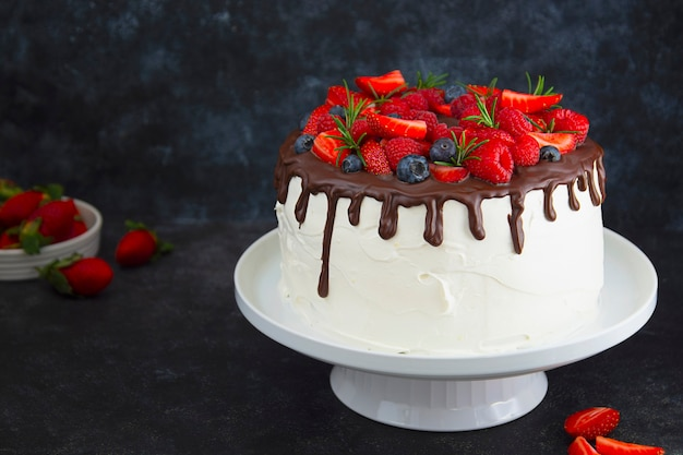 Weißer kuchen mit schokoladenglasur und frischen beeren auf dunklem hintergrund.