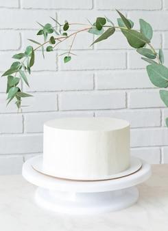 Weißer kuchen ohne dekor auf einem ständer unter einem zweig eukalyptus. kuchen mit kopierraum.