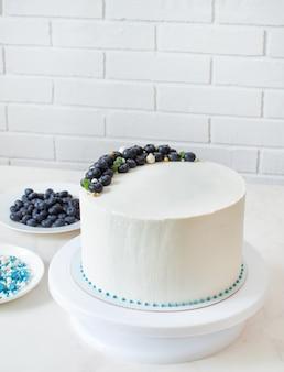 Weißer kuchen verziert mit blaubeeren und süßigkeiten auf einem ständer mit kopierraum.