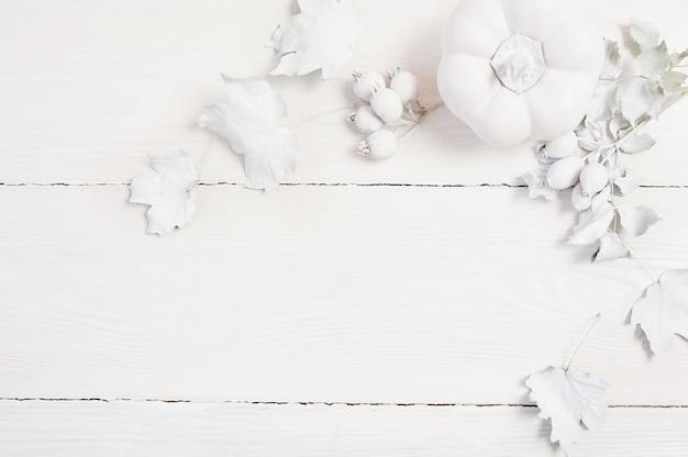Weißer kürbis, beeren und blätter des modells auf einem hölzernen herbsthintergrund
