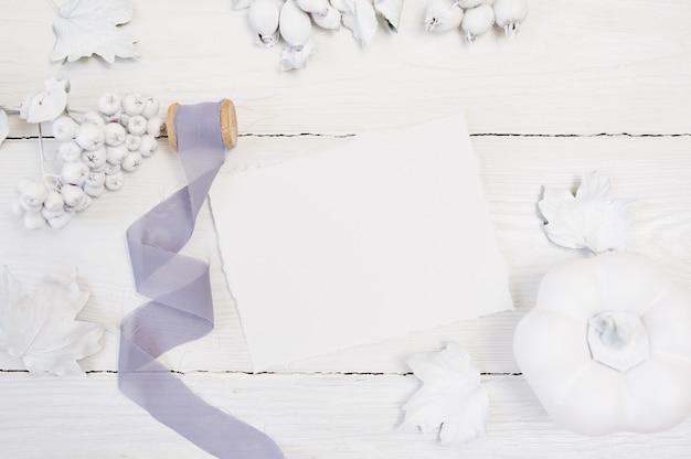 Weißer kürbis, beeren und blätter und graues band