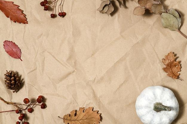 Weißer kürbis, herbstliche blätter und beeren auf braunem papier