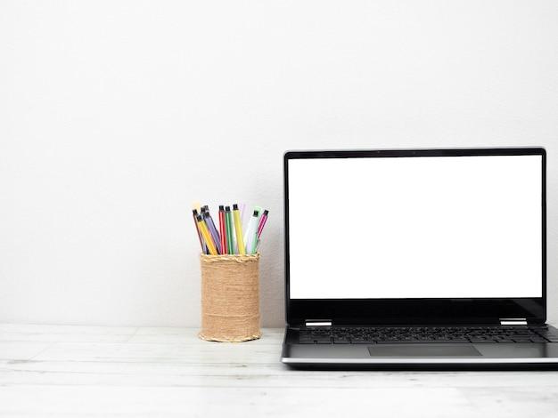 Weißer laptop-bildschirm mit stiftebox auf tischarbeitsplatz