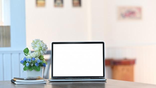 Weißer laptop mit leerem bildschirm, notebook, smartphone und topfpflanze, alles zusammen auf dem modernen schreibtisch