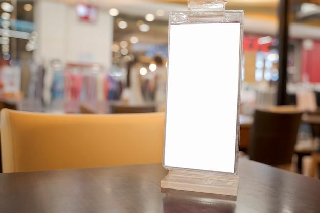 Weißer leerer aufkleber auf dem tisch. ständer für acrylzeltkarte